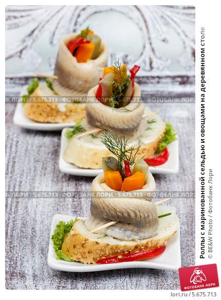 Купить «Роллы с маринованной сельдью и овощами на деревянном столе», фото № 5675713, снято 14 декабря 2018 г. (c) BE&W Photo / Фотобанк Лори