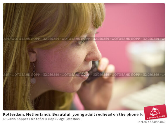 Rotterdam, Netherlands. Beautiful, young adult redhead on the phone for a phone call while working voluntarily at the Las Palmas Photo museum. Стоковое фото, фотограф Guido Koppes / age Fotostock / Фотобанк Лори