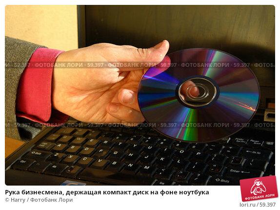 Рука бизнесмена, держащая компакт диск на фоне ноутбука, фото № 59397, снято 21 июня 2005 г. (c) Harry / Фотобанк Лори