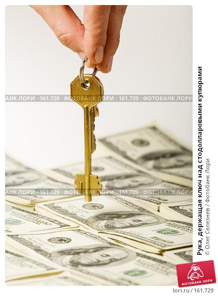 Рука, держащая ключ над стодолларовыми купюрами, фото № 161729, снято 26 декабря 2007 г. (c) Олег Селезнев / Фотобанк Лори