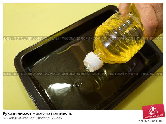 Купить «Рука наливает масло на противень», фото № 2041485, снято 7 октября 2010 г. (c) Яков Филимонов / Фотобанк Лори