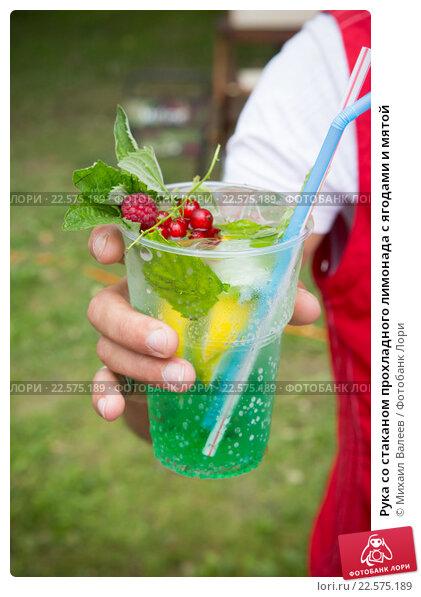 Купить «Рука со стаканом прохладного лимонада с ягодами и мятой», фото № 22575189, снято 25 июля 2015 г. (c) Михаил Валеев / Фотобанк Лори