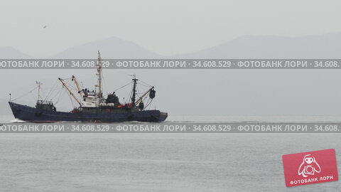Russian fishing vessel sailing in Pacific Ocean to fish in cloudy and rainy weather. Редакционное видео, видеограф А. А. Пирагис / Фотобанк Лори