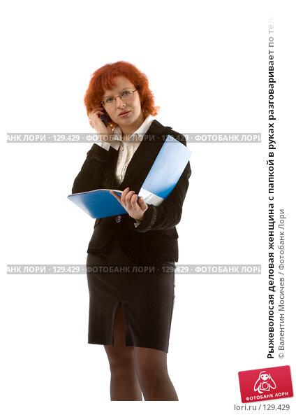Рыжеволосая деловая женщина с папкой в руках разговаривает по телефону Young businesswoman, фото № 129429, снято 18 марта 2007 г. (c) Валентин Мосичев / Фотобанк Лори