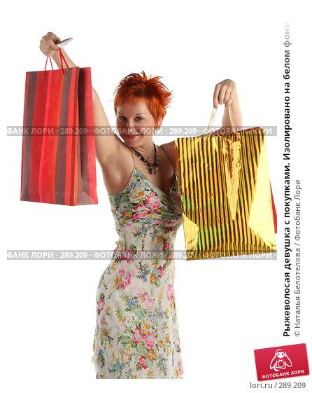 Рыжеволосая девушка с покупками. Изолировано на белом фоне, фото № 289209, снято 17 мая 2008 г. (c) Наталья Белотелова / Фотобанк Лори