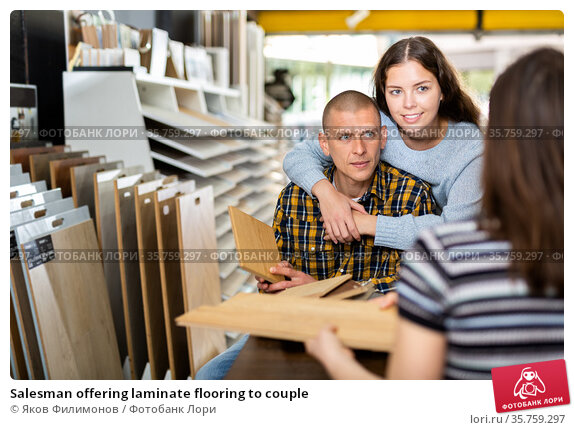 Salesman offering laminate flooring to couple. Стоковое фото, фотограф Яков Филимонов / Фотобанк Лори