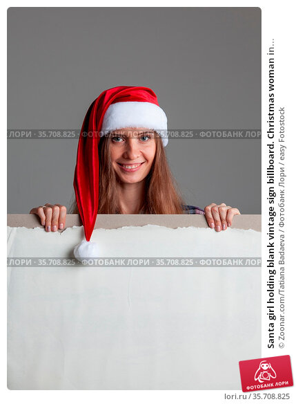 Santa girl holding blank vintage sign billboard. Christmas woman in... Стоковое фото, фотограф Zoonar.com/Tatiana Badaeva / easy Fotostock / Фотобанк Лори