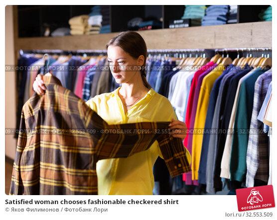 Купить «Satisfied woman chooses fashionable checkered shirt», фото № 32553509, снято 9 декабря 2019 г. (c) Яков Филимонов / Фотобанк Лори