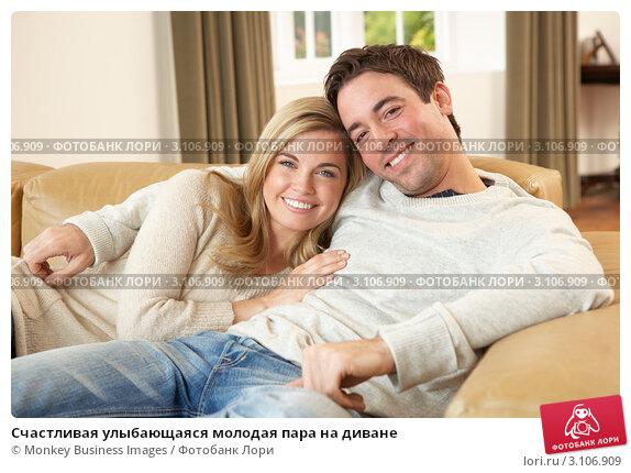Счастливая улыбающаяся молодая пара на диване, фото № 3106909, снято 11 ноября 2010 г. (c) Monkey Business Images / Фотобанк Лори