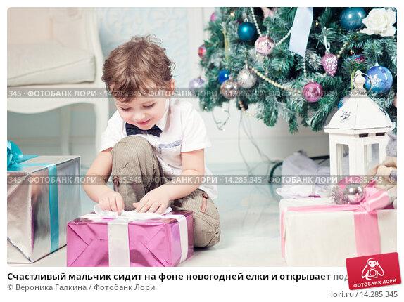 Купить «Счастливый мальчик сидит на фоне новогодней елки и открывает подарок», фото № 14285345, снято 26 декабря 2013 г. (c) Вероника Галкина / Фотобанк Лори