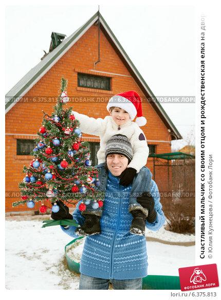 Счастливый мальчик со своим отцом и рождественская елка на дворе зимой. Стоковое фото, фотограф Юлия Кузнецова / Фотобанк Лори