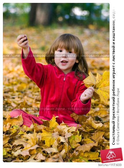 Счастливый трехлетний ребенок играет с листвой и каштаном, сидя на земле, фото № 117633, снято 1 октября 2007 г. (c) Ольга Сапегина / Фотобанк Лори