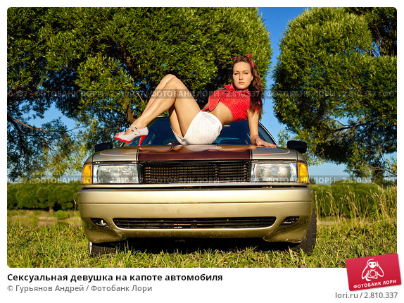 Сексуальная девушка сидит на капоте авто