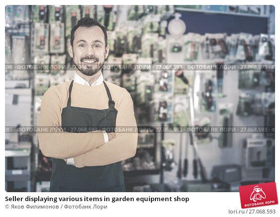 Купить «Seller displaying various items in garden equipment shop», фото № 27068593, снято 2 марта 2017 г. (c) Яков Филимонов / Фотобанк Лори