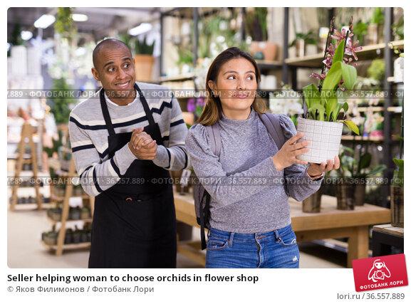 Seller helping woman to choose orchids in flower shop. Стоковое фото, фотограф Яков Филимонов / Фотобанк Лори
