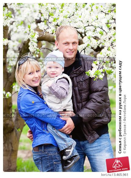 Семья с ребенком на руках в цветущем саду. Стоковое фото, фотограф Кирилл Греков / Фотобанк Лори