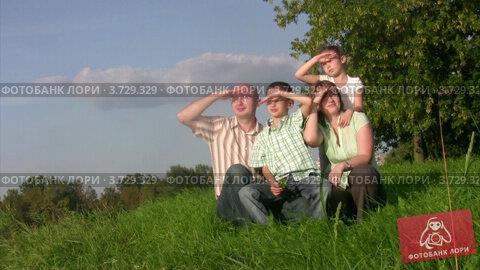 Купить «Семья сидит в траве и смотрит вдаль», видеоролик № 3729329, снято 6 апреля 2011 г. (c) Losevsky Pavel / Фотобанк Лори