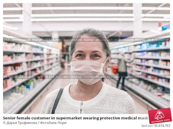 Senior female customer in supermarket wearing protective medical mask. Стоковое фото, фотограф Дарья Филимонова / Фотобанк Лори
