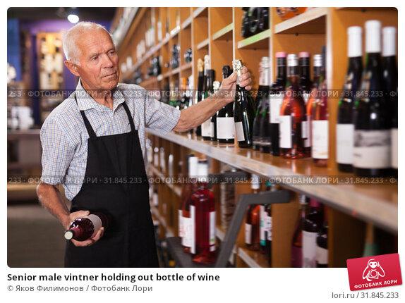 Купить «Senior male vintner holding out bottle of wine», фото № 31845233, снято 8 мая 2019 г. (c) Яков Филимонов / Фотобанк Лори