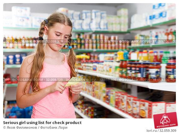 Serious girl using list for check product. Стоковое фото, фотограф Яков Филимонов / Фотобанк Лори