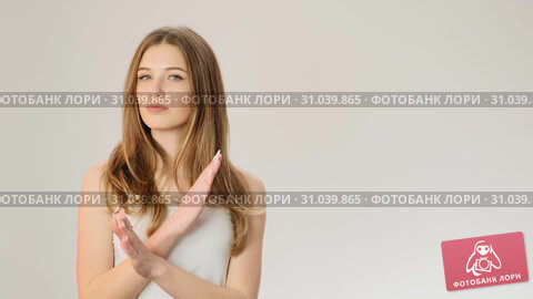 Serious young woman showing crossed hands gesture and looking at camera while standing isolated over gray background slow motion. Стоковое видео, видеограф Denis Mishchenko / Фотобанк Лори