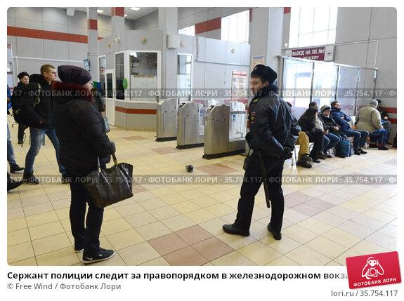 Сержант полиции следит за правопорядком в железнодорожном вокзале в Орехово-Зуево Московской области (2016 год). Редакционное фото, фотограф Free Wind / Фотобанк Лори