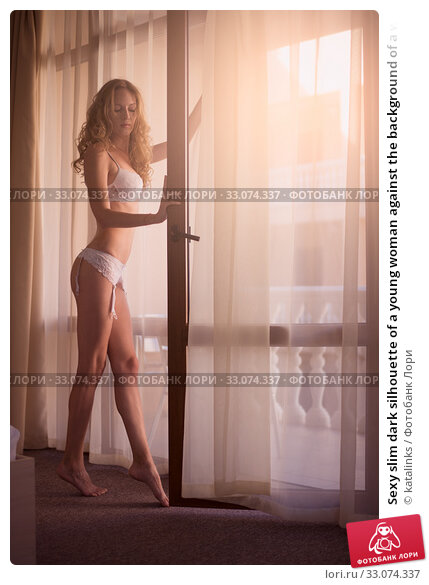 Купить «Sexy slim dark silhouette of a young woman against the background of a window with curtains and sun rays», фото № 33074337, снято 20 июля 2016 г. (c) katalinks / Фотобанк Лори