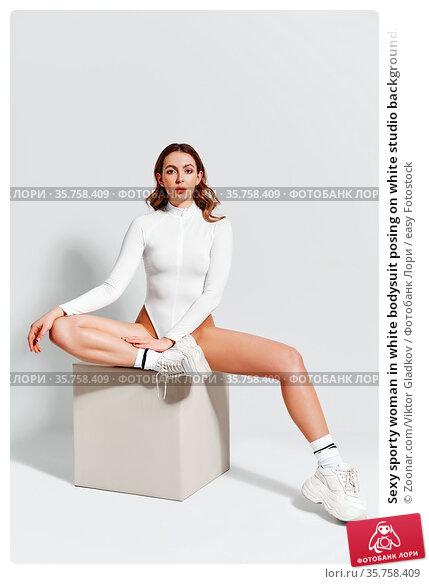 Sexy sporty woman in white bodysuit posing on white studio background... Стоковое фото, фотограф Zoonar.com/Viktor Gladkov / easy Fotostock / Фотобанк Лори
