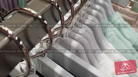 Купить «Сезон распродаж в магазине одежды. Вешалки с одеждой разных размеров.», видеоролик № 34071377, снято 10 июля 2020 г. (c) Мила Демидова / Фотобанк Лори