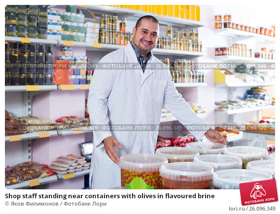 Купить «Shop staff standing near containers with olives in flavoured brine», фото № 26096349, снято 15 октября 2016 г. (c) Яков Филимонов / Фотобанк Лори