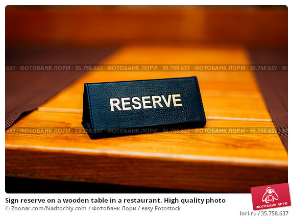 Sign reserve on a wooden table in a restaurant. High quality photo. Стоковое фото, фотограф Zoonar.com/Nadtochiy.com / easy Fotostock / Фотобанк Лори