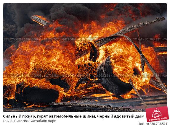 Купить «Сильный пожар, горят автомобильные шины, черный ядовитый дым в небе», фото № 30703521, снято 18 апреля 2019 г. (c) А. А. Пирагис / Фотобанк Лори