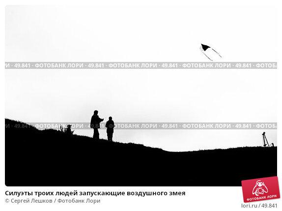 Силуэты троих людей запускающие воздушного змея, фото № 49841, снято 12 мая 2007 г. (c) Сергей Лешков / Фотобанк Лори