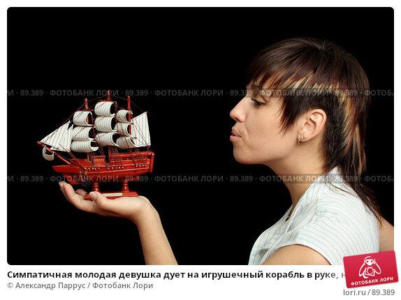 Купить «Симпатичная молодая девушка дует на игрушечный корабль в руке, на черном фоне», фото № 89389, снято 31 мая 2007 г. (c) Александр Паррус / Фотобанк Лори