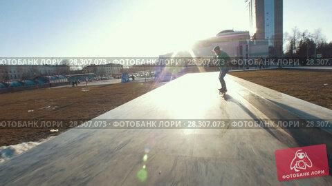 Купить «Skateboarder does tricks on the track outdoors in sunset», видеоролик № 28307073, снято 25 апреля 2018 г. (c) Константин Шишкин / Фотобанк Лори