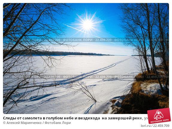 Следы от самолета в голубом небе и вездехода  на замерзшей реке, уходящие к горизонту, фото № 22459709, снято 27 марта 2016 г. (c) Алексей Маринченко / Фотобанк Лори