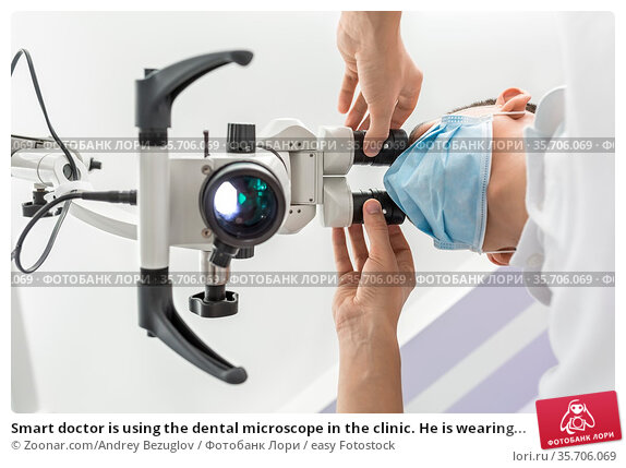 Smart doctor is using the dental microscope in the clinic. He is wearing... Стоковое фото, фотограф Zoonar.com/Andrey Bezuglov / easy Fotostock / Фотобанк Лори