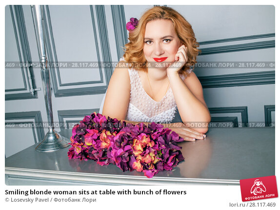 Купить «Smiling blonde woman sits at table with bunch of flowers», фото № 28117469, снято 14 ноября 2015 г. (c) Losevsky Pavel / Фотобанк Лори