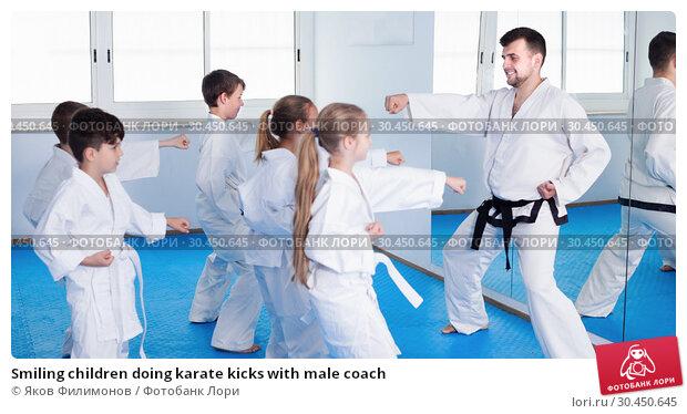 Smiling children doing karate kicks with male coach. Стоковое фото, фотограф Яков Филимонов / Фотобанк Лори