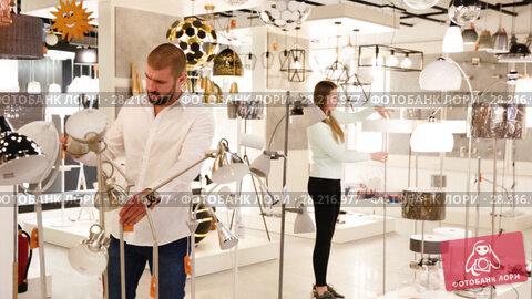 Купить «Smiling couple customers choosing floor lamp with a long standard in store», видеоролик № 28216977, снято 13 февраля 2018 г. (c) Яков Филимонов / Фотобанк Лори