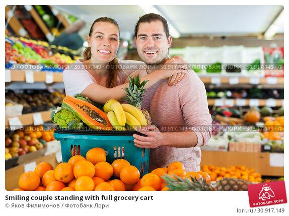 Купить «Smiling couple standing with full grocery cart», фото № 30917149, снято 27 апреля 2019 г. (c) Яков Филимонов / Фотобанк Лори