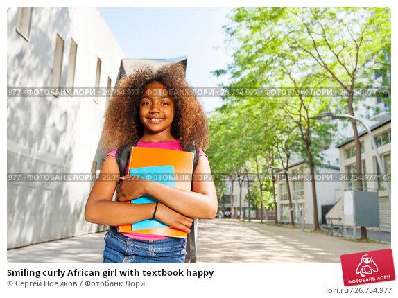 Smiling curly African girl with textbook happy, фото № 26754977, снято 17 июня 2017 г. (c) Сергей Новиков / Фотобанк Лори