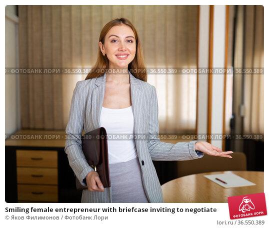 Smiling female entrepreneur with briefcase inviting to negotiate. Стоковое фото, фотограф Яков Филимонов / Фотобанк Лори