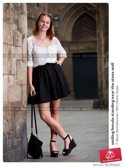 Купить «smiling female standing near the stone wall», фото № 32553621, снято 23 января 2020 г. (c) Яков Филимонов / Фотобанк Лори