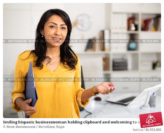 Smiling hispanic businesswoman holding clipboard and welcoming to office. Стоковое фото, фотограф Яков Филимонов / Фотобанк Лори