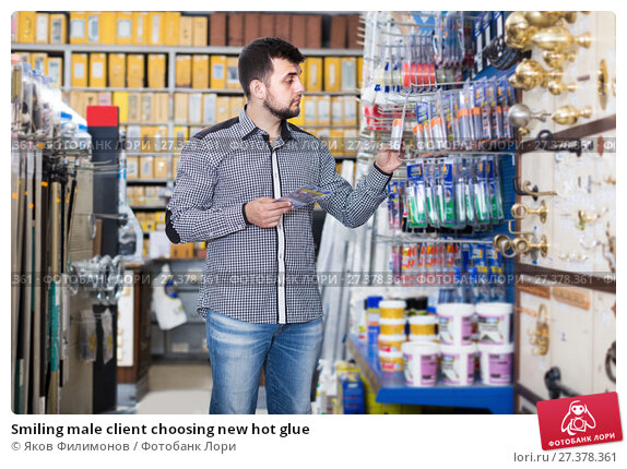Smiling male client choosing new hot glue. Стоковое фото, фотограф Яков Филимонов / Фотобанк Лори