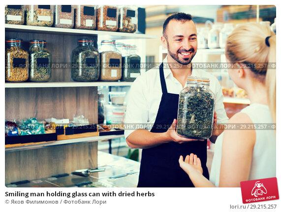 Купить «Smiling man holding glass can with dried herbs», фото № 29215257, снято 19 октября 2018 г. (c) Яков Филимонов / Фотобанк Лори