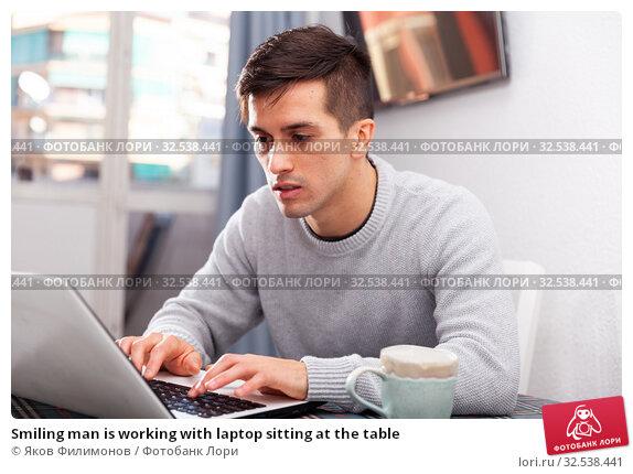 Купить «Smiling man is working with laptop sitting at the table», фото № 32538441, снято 9 декабря 2019 г. (c) Яков Филимонов / Фотобанк Лори