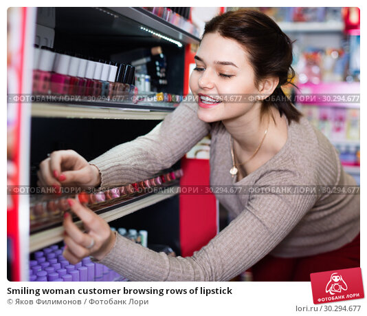 Купить «Smiling woman customer browsing rows of lipstick», фото № 30294677, снято 21 февраля 2017 г. (c) Яков Филимонов / Фотобанк Лори