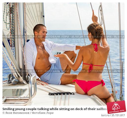 Smiling young couple talking while sitting on deck of their sailboat enjoying sea trip on sunny summer day. Стоковое фото, фотограф Яков Филимонов / Фотобанк Лори